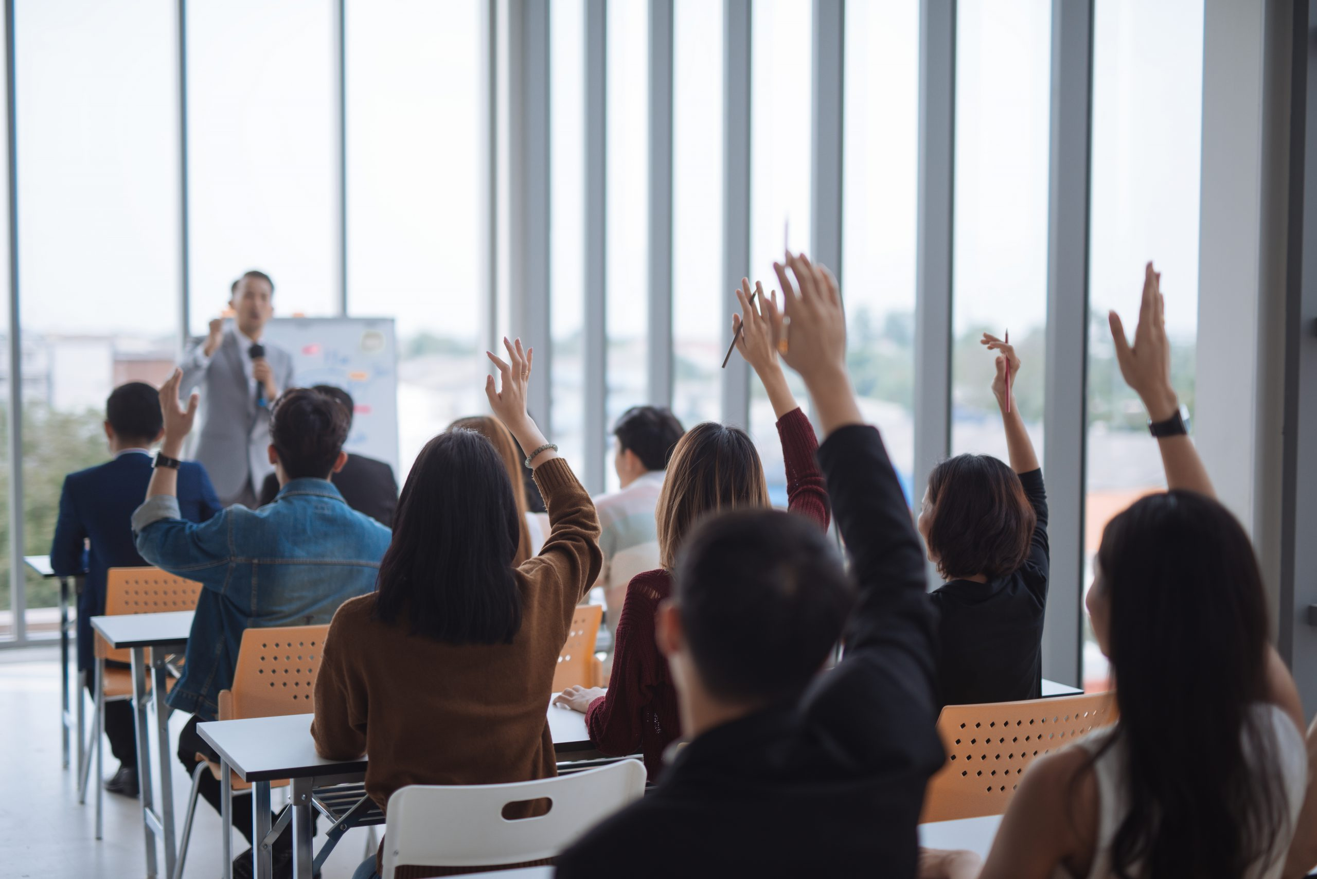 https://www.absolute-interpreting.co.uk/wp-content/uploads/2020/06/raised-up-hands-arms-large-group-seminar-class-room-agree-with-speaker-conference-seminar-meeting-room-scaled.jpg